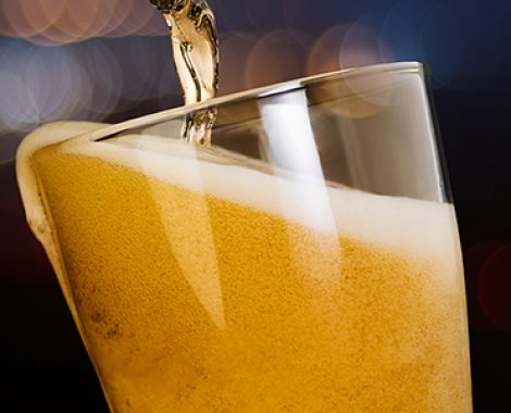 Motion of beer pouring from bottle into glass on bokeh light nig
